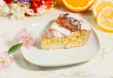 A piece of neapolitan easter pie sprinkled with icing sugar and decorated with almond blossom,freesia and fresh fruits. Royalty Free Stock Photography