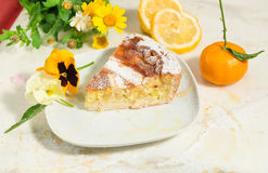 A piece of neapolitan easter pie sprinkled with icing sugar and decorated with spring flowers and fresh fruits. Royalty Free Stock Photography