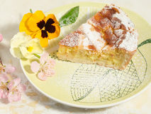 A piece of neapolitan easter pie sprinkled with icing sugar and decorated with spring flowers,pansy and fresh fruits. Royalty Free Stock Image