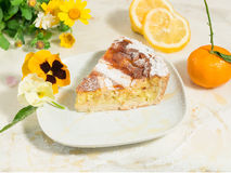 A piece of neapolitan easter pie sprinkled with icing sugar and decorated with spring flowers,pansy and fresh fruits. Royalty Free Stock Photography