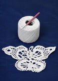 Piece of needlework near clue with crochet hook. White piece of needlework is put before a cotton bobbin of thread with a crochet hook Stock Image