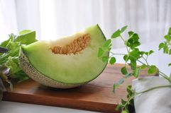 Piece Of Green Honeydew Melon On Wooden Cutting Board Stock Photo