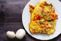 A piece of omelet on a white plate and two mushroom Royalty Free Stock Photo