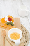 A piece of orange cake on a wood board Royalty Free Stock Image