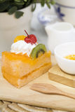 A piece of orange cake on a wood board. A piece of orange cake served on a wood board Stock Photography