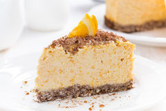 Piece of orange cheesecake on a plate, close-up Royalty Free Stock Photography