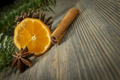 Orange, cinnamon and badian next to pine branch. Piece of orange, cinnamon and badian star anise next to pine branch and conifer cone, sitting on wooden table royalty free stock images
