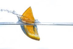 Piece on an orange falling into water with a splash. Piece on an orange falling into water with a big splash royalty free stock images