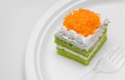 Piece of pandan cake with golden threads on top over plate royalty free stock photo