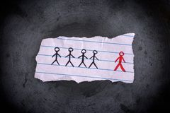 Piece of paper with drawn people and the red one is the odd one. Out. Concept Image. Close up Royalty Free Stock Images