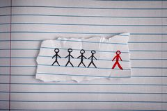 Piece of paper with drawn people and the red one is the odd one. Out. Concept Image. Close up Royalty Free Stock Image