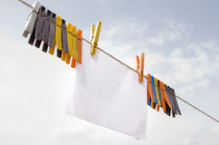 A piece of paper hanging on cord with clothespins Royalty Free Stock Images