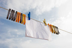 Piece of paper hanging on cord with clothespins Stock Photo