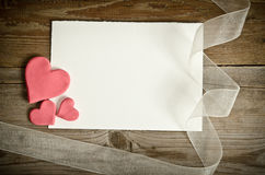 Piece of paper lying with hearts and ribbon Royalty Free Stock Photos