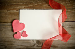 Piece of paper lying with hearts and ribbons Royalty Free Stock Photos