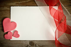 Piece of paper lying with hearts and ribbons Royalty Free Stock Images