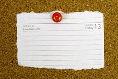 Piece of paper pegged to a cork board. Piece of paper showing the date Friday 13 pegged to a cork board stock images