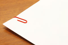 Piece of paper with a red clip on the table Royalty Free Stock Photo