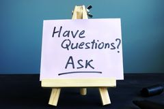 Piece of paper with sign Have questions Ask. Piece of paper with  handwritten sign Have questions Ask royalty free stock photography