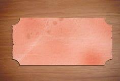 Piece of paper on wooden desk. Piece of orange frayed paper on wooden desk Royalty Free Stock Photos