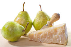 Piece of parmesan cheese with pear on cutting board Royalty Free Stock Image