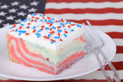 Piece of Patriotic Cake. Piece of cake with red white and blue sprinkles with american flag Stock Image