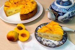 Piece of peach cake. On the table. Tea set Stock Photography