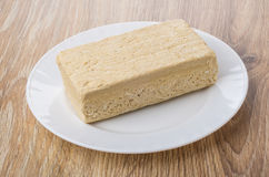 Piece of peanut halva in white plate on table Royalty Free Stock Photography