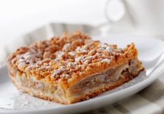 Piece of Pie. Close up picture of a baked pie on the plate with a cup at the back Royalty Free Stock Images