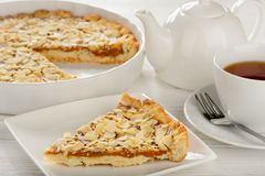 Piece of pie with carmel and almond and cup of tea. Royalty Free Stock Image
