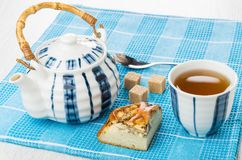 Piece of pie with chicken, teapot, sugar, tea, teaspoon Royalty Free Stock Images