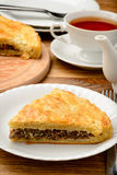 Piece of pie with minced meat on wooden table. Stock Photos