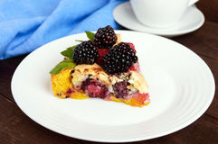 A piece of the pie (Tart) with fresh blackberries and raspberries, air meringue, mint decoration on a white plate. Stock Photos
