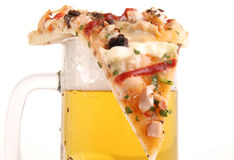 Piece of pizza on the beer mug royalty free stock photography