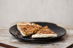 Piece of pizza on black plate. And on table Royalty Free Stock Images