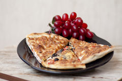 Piece of pizza with grapes. On black plate and on table Stock Image
