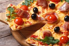 Piece of pizza with ham, tomatoes, black olives and arugula Royalty Free Stock Photo
