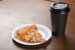 A piece of pizza in an individual cardboard box and a plastic cup for coffee Stock Photos