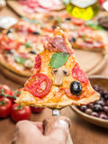 Piece of pizza with mushrooms, ham and tomatoes. Royalty Free Stock Image