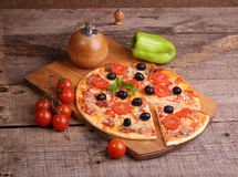 Piece of a pizza and pizza from a salami, a ham and tomatoes on Stock Photo