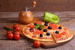 Piece of a pizza and pizza from a salami, a ham and tomatoes on. A wooden table royalty free stock photo