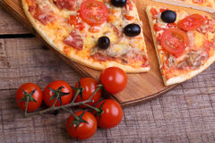 Piece of a pizza and pizza from a salami, a ham and tomatoes on. A wooden table royalty free stock images