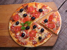 Piece of a pizza and pizza from a salami, a ham and tomatoes on. A wooden table stock photo