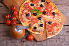Piece of a pizza and pizza from a salami, a ham and tomatoes on. A wooden table stock image