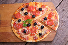 Piece of a pizza and pizza from a salami, a ham and tomatoes on. A wooden table royalty free stock image