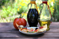 Piece of pizza in the summer garden table Royalty Free Stock Photos