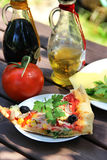 Piece of pizza in the summer garden table Royalty Free Stock Image