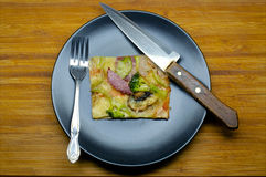 Piece of pizza. With vegetables on the black plate with knife and fork Royalty Free Stock Photography