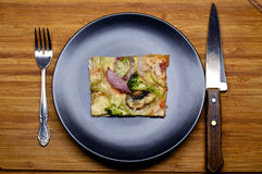 Piece of pizza. With vegetables on the black plate with knife and fork Stock Image