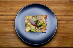 Piece of pizza. With vegetables on the black plate on the wooden background Stock Image